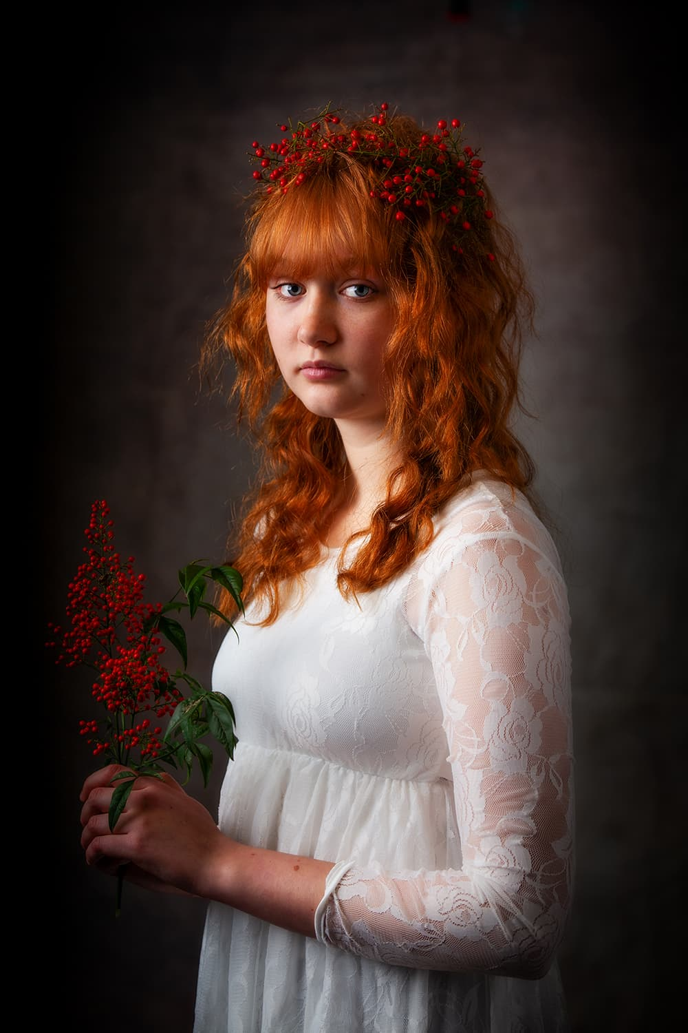 Teen portrait of a red haired girl holding red berries in a white dress.