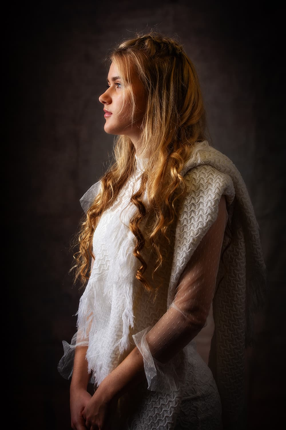 Low lit portrait of a teen profile wearing a white dress witha woollen throw over her shoulder.